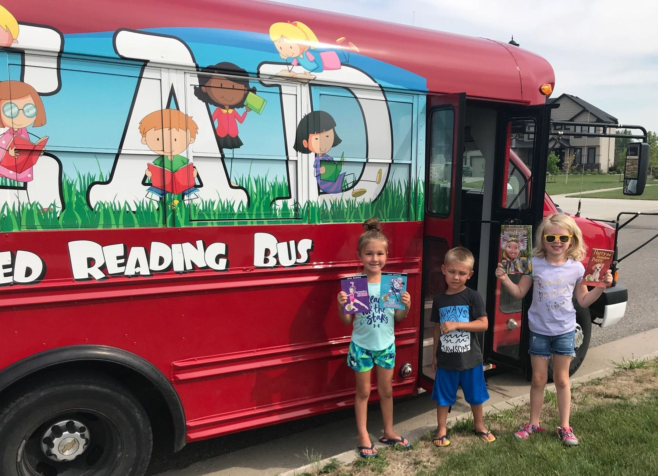 Kids standing in front of the Little Red Reading Bus